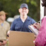 Home delivery. Men deliver large package to customer at her front door. She signs her name to delivery confirmation form on clipboard.  Mail order.  Men wear uniforms. Large cardboard box.