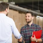 Two businessman shaking hands in warehouse.
