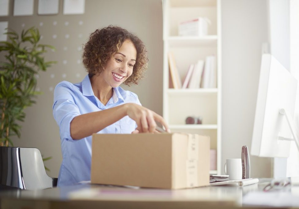 a young woman in her home office looks happy as she unpacks a small cardboard box containing something exciting